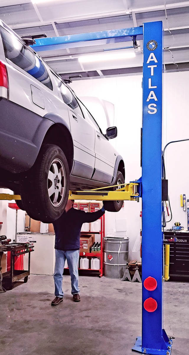 Jim Gamble working on Volvo on lift